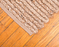 Jute pile hand woven rug. Jute pile hand woven beige area rug on old hardwood floor Royalty Free Stock Images