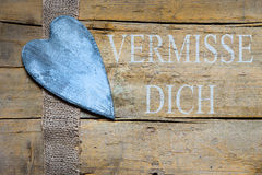 Jute ribbon and heart on wooden table, german text, concept miss Royalty Free Stock Photo