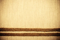 Jute ribbon on linen cloth background Royalty Free Stock Images