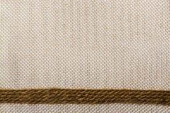 Jute ribbon on sack cloth background Royalty Free Stock Image