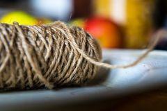 Jute string roll close up in vintage enamel plate on blurred background stock images