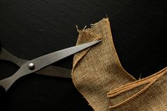 Jute tape with scissors on black background Royalty Free Stock Images