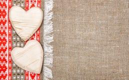 Juteachtergrond die door de doek van het land en houten harten wordt gegrenst Royalty-vrije Stock Afbeelding