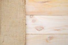Juteleinwandsackbeschaffenheit und Holztabellenhintergrund Stockfotos