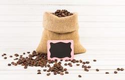 Jutepåse av grillat kaffe med den lilla svart tavlan Arkivfoton