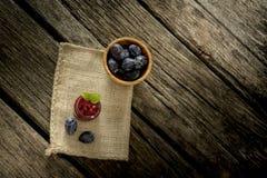 Jutezak die over rustiek geweven houten bureau met glaskruik liggen Stock Foto