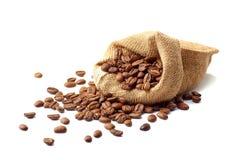 Jutezak met koffiebonen op wit royalty-vrije stock afbeelding