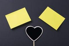Jutno amarelo do post-it dois a um quadro-negro com forma do coração no fundo preto Fotografia de Stock