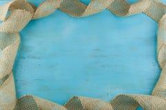 Jutowa faborek rama na błękitnym drewnianym tle Zdjęcie Royalty Free