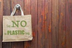 Jutowa torba bez plastikowego loga obwieszenia na starej drewnianej ścianie fotografia stock