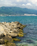 Jutting into the sea from the breakwater mound of stones. The black sea city of Novorossiysk Stock Photos
