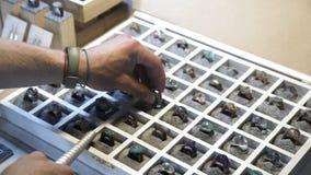Juvelerare genom att använda en mäta pinne, mått formatet av cirklarna av ädelstenar arkivfilmer