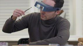 Juvelerare som kontrollerar kvaliteten av den briljanta ädelstenen till och med exponeringsglas Arkivfoton