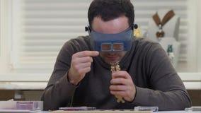 Juvelerare som ser dimondcirkeln till och med exponeringsglas i ett seminarium Arkivfoton