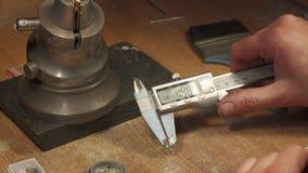 Juveleraren mäter ädelstenar på seminariumbänken royaltyfri foto