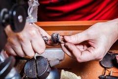 Juveleraren polerar det guld- örhänget Arkivbilder
