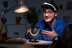 Juveleraren som sent arbetar i hans seminarium på natten Arkivbild