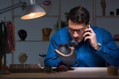 Juveleraren som sent arbetar i hans seminarium på natten Royaltyfri Bild