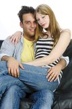 Juvenile couple snuggling on the sofa Royalty Free Stock Photo