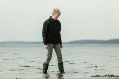 Juventud adolescente que camina en agua durante alta marea Imágenes de archivo libres de regalías
