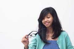Muchacha asiática hermosa que comprueba sus nuevos vidrios imagenes de archivo