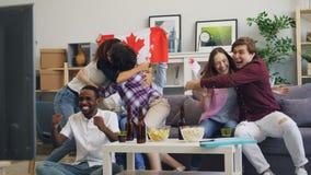 Juventud canadiense con las banderas que mira deportes en hacer de la TV alto-cinco y el abrazo almacen de video