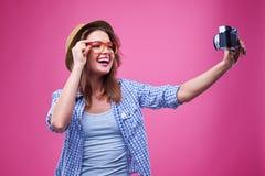 Juventud divertida que lleva los vidrios anaranjados y que hace una foto del selfie Foto de archivo libre de regalías