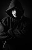 Juventud encapuchada contra fondo oscuro Imagen de archivo
