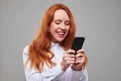 Juventud feliz que sostiene el teléfono móvil en manos Fotografía de archivo libre de regalías