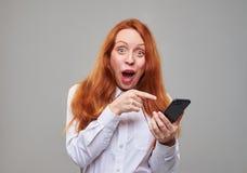 Juventud impresionada que señala el dedo índice en el SCR del smartphone Fotos de archivo libres de regalías