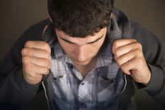 Juventud intensa que sostiene sudadera con capucha hasta cara foto de archivo libre de regalías
