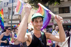 Juventud sonriente con el indicador del arco iris en el desfile TA del orgullo Imagen de archivo