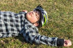 Juventude do menino que encontra-se na grama que toma sol no sol com sua bicicleta Foto de Stock Royalty Free