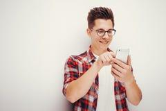Juventude e tecnologia Retrato do estúdio do homem que usa o telefone esperto Isolado fotografia de stock royalty free
