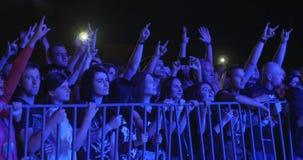 A juventude gesticula o metal pesado e as mãos de ondulação no concerto de rocha na noite video estoque