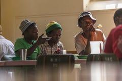 Juventudes africanas que comen en refugio Fotos de archivo libres de regalías