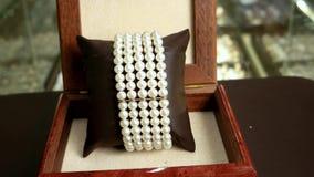 Juwelen die van parels, klassieke juwelen voor dames, parelhalsband, armband dure parel in een doos worden gemaakt die van mahoni stock footage
