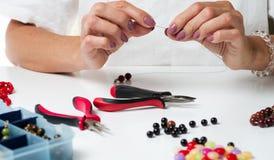 Juwelen het maken Het maken van armband van kleurrijke parels Vrouwelijke handen met een hulpmiddel stock foto's