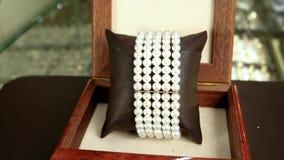 Juwelen, het product van de Halsbandparel in de armbanden van de de opslagparel van elitejuwelen in bruine houten kist, klassieke stock video