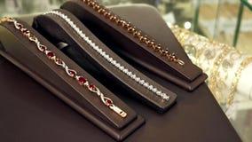 Juwelen, Kostbare juwelenarmbanden met robijnen en diamanten op een overzicht van de de gedraaide opslag, Edele metalen en de ste stock footage