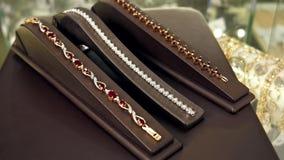 Juwelen, Mooie fonkelende glanzende gouden de armbanden Gouden ketting van juwelen Kostbare juwelen met robijnen op een tribune v stock videobeelden