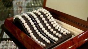 Juwelen, Overzichtsjuwelen die van parels op een mooie verlichte tribune worden gemaakt, Parelarmbanden in bruine houten kist stock videobeelden