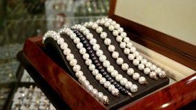 Juwelen van parels, Parelarmbanden op een voetstukdecoratie worden gemaakt voor betoverende fashionistas, klassieke juwelen voor  stock videobeelden