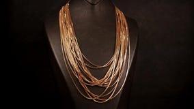 Juwelen, Veel gouden kettingen voor de eigenlijke rijke vrouwen op de tribune in een opslag, die voor verkoop in een juwelenopsla stock videobeelden