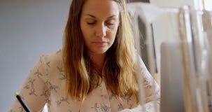 Juwelenontwerper die laptop met behulp van terwijl het schrijven op nota 4k stock footage