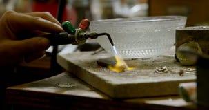 Juwelenontwerper die met het hanteren van toorts in workshop 4k werken stock footage