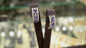 Juwelenopslag, juwelenreeks, in de oorringen van de juwelenopslag met stenen, oorringen, ringen, tegenhangers, kettingen van goud stock videobeelden