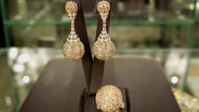 Juwelenopslag, juwelenreeks, Oorringen en een ring van goud die met juwelen, dure modieuze gift, Briljant wordt behandeld verkoch stock videobeelden