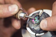 Juwelier bedrängt Edelstein in einem Produkt vom Weißgold das Spezialwerkzeug für ein Clip von Steinen lizenzfreies stockfoto