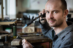 Juwelier het zilveren solderen in zijn workshop Stock Foto's
